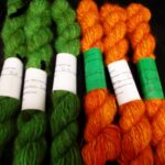 Handspun hand dyed 100% angora yarn in dark orange and jungle green. d.k. weight